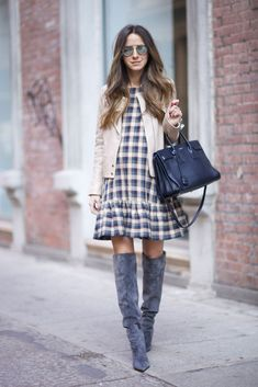 Lovely, simple layering with a cute ruffled dress, short boxy jacket and long boots.... Plaid is a classic trend! Arielle Nachami wears a cute plaid midi dress with over the knee boots and a casual tan jacket. Wear the look with tights if you have to brave the cold! Dress: The Great, Boots: Gianvito Rossi, Jacket: J Brand, Bag; Saint Laurent.