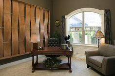 One of the most intriguing walls we have seen with its unique wood wall art highlighting this traditional home office. It gives the remodeled office a mid-century modern sense with a cozy side chair, black leather tufted office chair and beige carpeted floors. Love the large window treatment.
