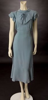 Here is a day dress from 1932. The day dresses of this time were longer than the 1920s. They usually hit the calf and had slightly higher waistlines than the natural waistline.