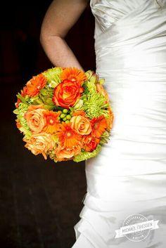 Round Bridal Bouquet Comprised Of: Orange Gerbera Daisies, Orange Roses, Green Spider Mums, Green Button Mums, Green Succulent + Green Hypericum Berries