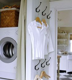 Hooked on Storage  If your laundry room lacks enough depth for a traditional clothing bar, mount multiple double-hooks to a wall.