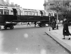 An underground train being transported on wheels through the streets of London, Note the steam traction engine ! London Underground Train, London Underground Stations, Underground Tube, London History, British History, Vintage London, Old London, London Life, London Street