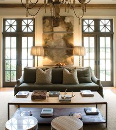 Adore the layered artwork, French Chandy, tapered sofa in olive green matching the French doors. Fabulous den!