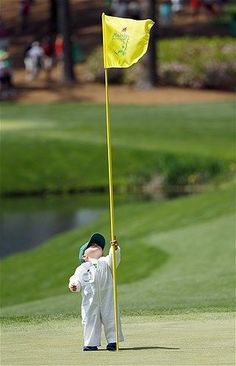 The son of pro golfer Scott Stallings plays with the flag on the fourth green during the par three competition at the Masters golf to...