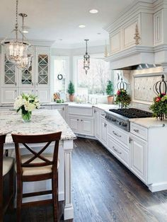 White kitchen, corner farmhouse sink, pendant lights, granite, back splash, wood floors.