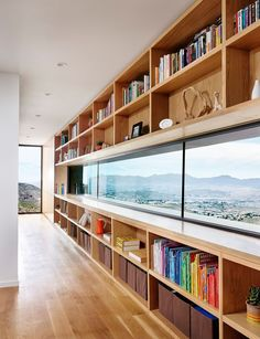 In this modern house, white oak open shelving surrounds a horizontal letterbox window, while the floor-to-ceiling window looks out on the landscape and city below
