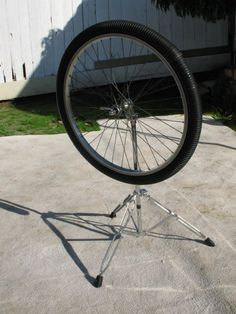 """This """"Rain Wheel"""" is a corrugated hose filled with rocks, beans, BBs, etc., and attached to a bicycle rim with zip ties. Can be mounted on a fence or wall as part of an outdoor music area."""