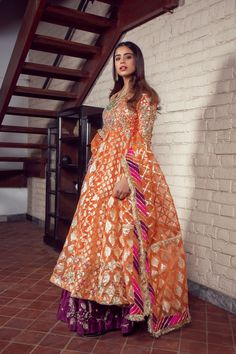 Best 12 This tangerine kalidar pishwas is lavishly embroidered with gota patti work in resham and tilla, plum hand worked kalidaar lehnga and accommpanied with a suchi kiran dupatta. Perfect for summer sangeet/mehndi. This is a complete mehndi brid Pakistani Fancy Dresses, Pakistani Wedding Outfits, Pakistani Dress Design, Bridal Outfits, Indian Dresses, Pakistani Mehndi Dress, Pakistani Couture, Indian Suits, Punjabi Suits