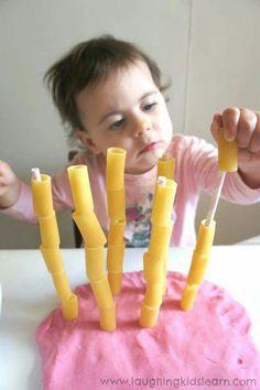 Pastatorens: neem klei en prik er satéprikkers op. Neem dan de pasta en laat de peuter de pasta over de satéprikkers doen. Dit stimuleert de fijne motoriek door dat het kind met zijn vingers de pasta om de satéprikker moet doen.
