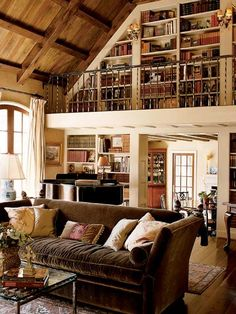 At the end of this living room, a full-height library wall includes balcony access. The book-lined wall, wood ceiling, and wide-plank floor give the room visual warmth. Such a great idea for high ceiling homes to make use of that wasted space.(Photo: Photo: Cheryl Dalton