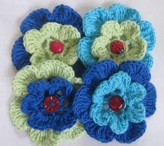 1 Sett med 4 hekla blomster, i blått, turkis og lys grønn.