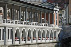 The present market, built by the architect Jože Plečnik between 1940 and 1944, was conceived as a two-storey range of riverside market halls following the curve of the river.