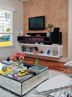 Por trás da TV, um painel de drywall, afastado 7 cm da alvenaria, esconde a fiação dos aparelhos – o efeito marmorizado foi obtido com uma textura comprada pronta. Dois nichos de diferentes alturas, um de laca branca brilhante e o outro de laminado fosco púrpura, abrigam os CDs e DVDs. Piso de madeira.