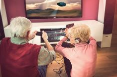 Senior adult couple playing video games in living room stock photo