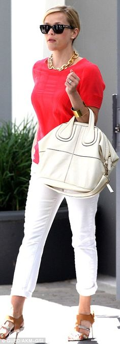 Bold accessories: The Reese wore a chunky gold necklace and cuff bracelet and carried a large cream leather handbag