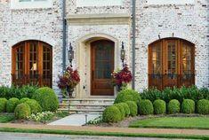 Os tijolos claros combinaram perfeitamente com esta fachada, cercada pelo verde e com flores cor bordô. Destaque para os janelões e porta de madeira.