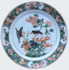 Assiette à décor de martin-pêcheurs en porcelaine de Chine d'époque Kangxi. Porcelaine de la Compagnie des Indes.  Peinte dans les émaux de la famille verte, à décor de martin-pêcheurs parmi des pivoines. Sur l'aile, des cartouches renfermant des cigales.