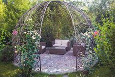 Folly gazebo in garden with metal frame outdoor furniture and rose bushes