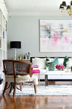 Modern, eclectic and feminine living room with pops of pink and green against a black white and gray backdrop. Chic accessories, palm pillows, abstract art, black shades.
