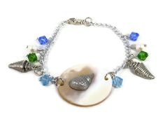 This Just Beachy Charm Bracelet with Swarovski Bicones is looking for a wrist going to the beach! I used Swarovski Bicones (6mm Sapphires, 6mm Aquamarine, and 6mm Fern Green) to represent the ocean; Swarovski Pearls 6mm, and 15 X 8mm cone shell antiqued pewter charms to represent the things found in the ocean. This fun Just Beachy Charm Bracelet with Swarovski Bicones is approx. 7 inches long. Wear this bracelet for casual parties or events! This bracelet will look great with a tank top and…