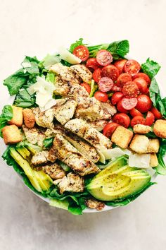 A mouthwatering classic salad with juicy grilled chicken, crisp romaine lettuce, cherry tomatoes, avocado, and topped with mozzarella and crunchy croutons!
