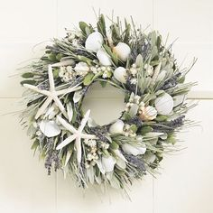 Like a memento from a walk down a sandy beach and through wild coastal grasses, this hand-assembled wreath displays a collection of shells and botanicals. White starfish and other natural sea shells from the Pacific Ocean – conches, sand dollars, cone shells and scallops – intermingle with fragrant blue English lavender, sage-green integrifolia leaves and bear grass, all on a base of natural twigs.
