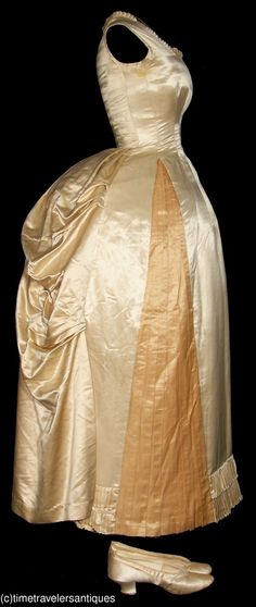 """""""A simple yet elegant original circa 1888 ivory silk satin one piece evening gown with a fashionable bunted bustle that was a popular style for young women."""""""