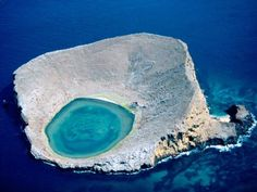 Galápagos Lagoon.  As startling as a bright-blue eye, a central lagoon peers out from Rocas Baimbridgen in Ecuador's Galápagos Islands. The stark, rocky island teems with life at times—the brackish lagoon waters are favored by flamingos
