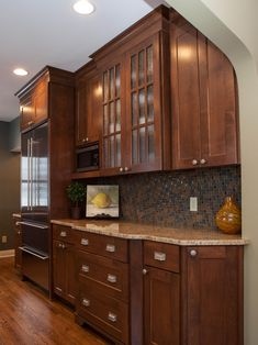 This craftsman style home was built in the 1940s and remodeled to preserve the historical character while adding modern amenities. The updated kitchen features Alder cabinetry with glass-front cabinets and an understated backsplash that brings out the warm browns in the wood.