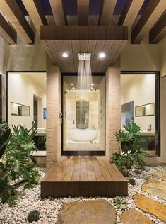 This bathroom boasts an open shower area with a wooden platform, flagstone path and pebble flooring, separated from the rest of the bathroom by a glass door. Succulents and other plants give the space a natural feel.