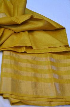 mustard yellow pure tussar silk saree with gold double sided border and the gold striped pallu. Comes with an attached blouse. Measurements:Saree : Length - 5.5
