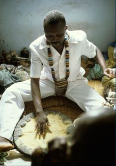 Africa   Yoruba priest Kolawole Ositola begins the rite of divination by marking a crossroads pattern in the powdered surface of the divination board. He uses an ivory tapper to invoke the presence of ancient Ifa priests. Porogun Quarter, Ijebu-Ode, Nigeria, 1992   Image ©John Pemberton III