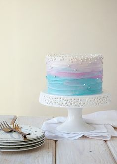This ombre blue, purple, and white cake with edible pearls would be so perfect…