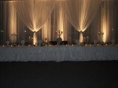 Backdrop of chiffon drapery and lighting accents, forefront for the head table chiffon and rhinestone brooches.  #wedding backdrop  #head table  #bridal party table