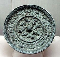 Bronze mirror, Tang Dynasty, 618-907 AD.  City Museum, Luoyang.  The mirror carries an elaborate design of auspicious animals and grapes; its knob is shaped like a frog.