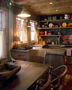Love the rustic shelves with the wood branches holding up the corners. The use of flour sack for the curtains. Rustic wood cabinets, floors and well used wooden table.