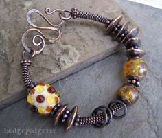 On a heavy gauge solid copper wire core, Mykonos Greek ceramic beads that have been dipped in pure copper and amber-hued artisan lampwork beads provide an interesting contrast of light and texture. Solid jump rings provide a bit of movement while a dark rich patina brings out the warmth of the copper and highlights this bracelet's richly textured design. A handmade hammered wiredoodle clasp further enhances its unique handcrafted look.