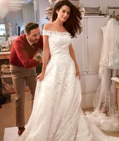 Amal Alamuddin married George Clooney on September 27, 2014 in Venice, Italy. The bride's off-the-shoulder gown was designed by Oscar de la Renta. It was made of ivory tulle appliquéd with 14 yards of French Chantilly lace, its bodice hand embroidered with beading and crystals. Her cathedral-length veil, was also adorned with French Chantilly and bead-and-crystal embroidery.