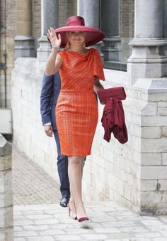 The queen in an orange dress by Natan. Click on the image to see more looks.