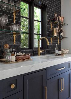 shiny black subway tile, glass shelving with gold brackets, chunky marble counters, black cabinets, gold hardware, black windows over sink