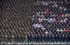 Pedro Ugart, AFP / Getty Images: April 14, 2012. North Korean soldiers, left, share seats with civilians during an official ceremony attended by leader Kim Jong-Un at a stadium in Pyongyang.