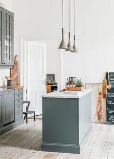 """Den grå kulören gör att köket känns mer intimt och samlat. Kök från Marbodal med platsbyggda detaljer. Lampor i betong """"Aplomb"""" från Foscarini. Liten grå pall från Ikea. Styckningsplanschen är vintage från en liten butik i Göteborg som heter Out of Fashion. Menyn kommer från restaurangen nedanför lägenheten."""