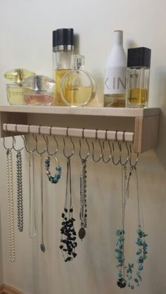 This is an Ikea spice rack. We flipped the mounting hardware and mounted the shelf upside down. Then hung shower curtain rings to hang jewelry on.