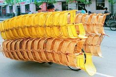 """A cyclist transports decks of chairs on his bicycle in Zhengzhou in central China's Henan Province"""