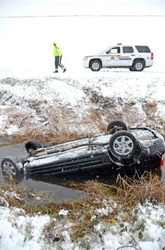 An RCMP officer on the scene of a car rollover on Gibson Road Wednesday around noon. The woman was trapped in her car in the water-filled ditch and had to be rescued by police. Car Ins, Wednesday, Police, Scene, Times, Woman, Water, Gripe Water, Law Enforcement