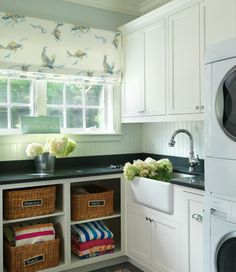 laundry/mud rooms - farmhouse sink white cabinets black countertops baskets white washer dryer roman shade white blue laundry room  Gorgeous