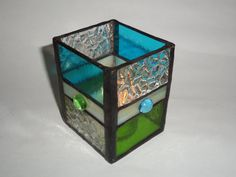 This Stained Glass Candle Holder was designed by me and made using the Tiffany Copper Foil Method. It measures 3 1/4inX3in and is 4in high.I chose watery blue and peridot green glass and a sparkly textured clear glass to reflect the candles glow. Each side of the candle holder is accented with an alternating blue or green glass pebble on the vanilla band lending to a beachy feel. The completed piece has a black patina for a traditional look. A tea light candle is included for instant…