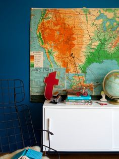 This youthful vignette is created by pairing a white lacquer modern piece with a collection of vintage school maps, globes and ephemera. The turquoise and red color palette is bold, fresh and exciting. The metal chair, typically used outside, brings in an extra dose of whimsy. Discover more kids room decorating and organizing tips and ideas @ http://kidsroomdecorating.net
