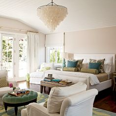 Like the colors and the large bedroom with room for seating and the turquoise tufted ottoman/coffee table.