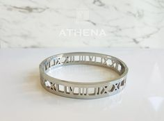 Steal the spotlight with this bold & beautiful Roman Empress bangle. Two sleek metallic silver bands connected with classic Roman numerals. This piece adds a touch of luxury to any casual or formal outfit. Silver Bangles, Silver Rings, Wedding Rings, Engagement Rings, Band, Luxury, Metal, Beautiful, Jewelry